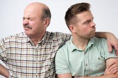 Deux hommes mûrs engendrent et le fils sont offensés sur l'un l'autre Ayez un désaccord photos libres de droits