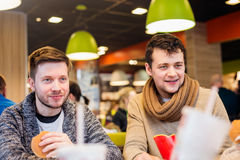 Deux hommes mangeant dans le restaurant d'aliments de préparation rapide, parlant Images stock