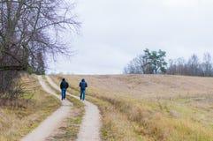 Deux hommes marchant par la route rurale coudée Images stock