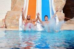 Deux hommes montant en bas des glissière-amis d'une eau appréciant un tube de l'eau montent Image libre de droits