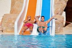 Deux hommes montant en bas des glissière-amis d'une eau appréciant un tube de l'eau montent Photographie stock
