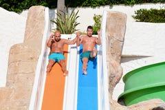 Deux hommes montant en bas des glissière-amis d'une eau appréciant un tube de l'eau montent Image stock