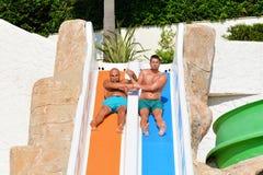Deux hommes montant en bas des glissière-amis d'une eau appréciant un tube de l'eau montent Photos libres de droits