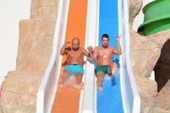 Deux hommes montant en bas des glissière-amis d'une eau appréciant un tube de l'eau montent Photo libre de droits
