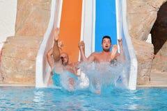 Deux hommes montant en bas des glissière-amis d'une eau appréciant un tube de l'eau montent Photos stock