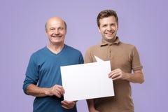 Deux hommes montrant le copyspace vide pour l'annonce images libres de droits