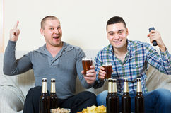 Deux hommes observant le football avec de la bière d'intérieur Photographie stock libre de droits