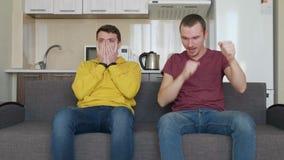 Deux hommes observent un match de football sur différentes équipes de TV et de soutien banque de vidéos
