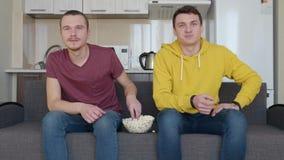 Deux hommes observent une partie de football et mangent du maïs éclaté clips vidéos