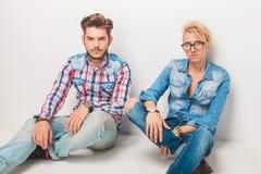 Deux hommes occasionnels songeurs s'asseyant sur le plancher Photos libres de droits
