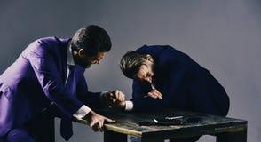 Deux hommes ou hommes d'affaires luttant avec les bras, combat pour la direction Photos stock