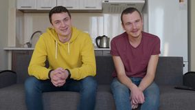Deux hommes parlent et sourient Les jeunes types drôles s'asseyent sur le divan et rient de la plaisanterie clips vidéos
