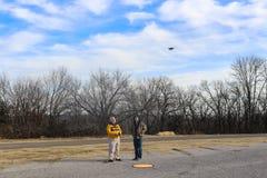 Deux hommes pilotant un DJI étincellent avec un contrôleur pendant l'hiver - aire d'atterrissage vertical sur la terre devant eux Images libres de droits