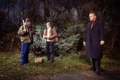 Deux hommes plus âgés sans abri ont rencontré l'homme de directeur dans le costume en parc d'hiver Image libre de droits