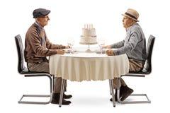 Deux hommes pluss âgé aux bougies de soufflement d'une table sur un gâteau photographie stock