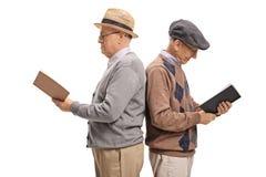 Deux hommes pluss âgé avec leur livre de lecture de dos les uns contre les autres Image libre de droits