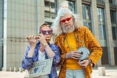 Deux hommes pluss âgé de hippie encourageant des personnes pour donner l'amour Images stock