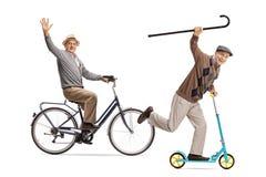 Deux hommes pluss âgé montant une bicyclette et un scooter et ondulant au Photographie stock