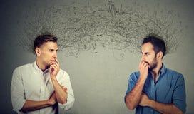 Deux hommes préoccupés regardant l'un l'autre échangeant des pensées Image stock