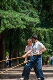 Deux hommes pratiquent Bojutsu en parc de Retiro à Madrid image libre de droits