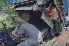 Deux hommes réparent le camion, travaillent dur sur un jour chaud photos stock
