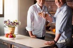 Deux hommes rasing des verres dans la cuisine Images stock