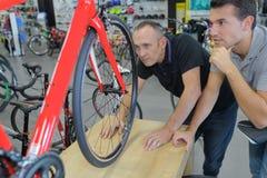 Deux hommes regardant la bicyclette sur la plate-forme augmentée photos stock