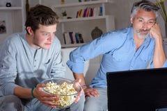 Deux hommes regardant la télévision tenir le maïs éclaté de cuvette Images stock