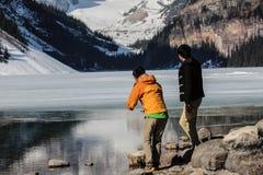 deux hommes regardant Lake Louise et montagnes Photographie stock libre de droits