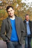 Deux hommes restant à l'extérieur dans la régfion boisée d'automne Image libre de droits