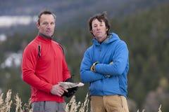 Deux hommes restant dans la région sauvage avec une carte Images stock