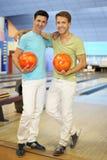 Deux hommes restent ensemble dans le club de bowling Images libres de droits