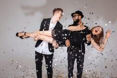 Deux hommes riant et tenant la femme avec le verre de champagne Photographie stock
