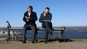 Deux hommes s'asseyant dehors sur un banc avec un livre Photographie stock