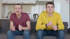 Deux hommes s'asseyant le divan et le moment d?cisif de observation du match de football banque de vidéos