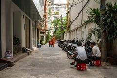 Deux hommes s'asseyant sur des tabourets dans une allée Photo stock