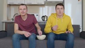 Deux hommes s'asseyant sur le divan observent un match de football ? la TV et ma?s ?clat? de consommation banque de vidéos