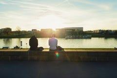 Deux hommes s'asseyant sur le remblai Cracovie du ` s de ville, appréciant le coucher du soleil Images stock