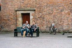Deux hommes s'asseyant sur un banc de publick au centre historique d'Utrecht Photo libre de droits