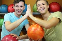 Deux hommes s'asseyent près des étagères dans le club de bowling Image stock
