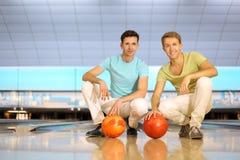 Deux hommes s'asseyent sur l'étage avec des billes dans le club de bowling Photos libres de droits