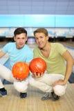 Deux hommes s'asseyent sur l'étage avec des billes dans le club de bowling Photo stock