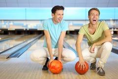 Deux hommes s'asseyent sur l'étage avec des billes dans le club de bowling Images libres de droits