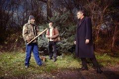 Deux hommes sans abri attaquant le directeur dans le costume passant par le parc Photographie stock libre de droits