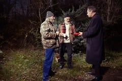 Deux hommes sans abri ont rencontré l'homme dans le costume en parc d'hiver Photo libre de droits