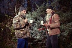 Deux hommes sans abri partageant leur solitude en parc d'hiver Photos libres de droits