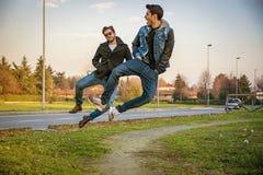 Deux hommes sautant à l'unisson avec des mains dans des poches Photo libre de droits