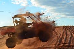 Deux hommes sautant des quatre Wheeler Over une dune de sable Images stock