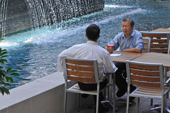 Deux hommes se réunissant près d'une fontaine. Photo libre de droits