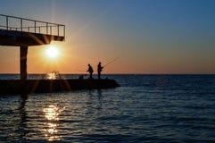 deux hommes se tiennent sur le pilier et les poissons avec une canne à pêche Images libres de droits